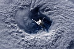 Space ship shuttle flying near earth from the hurricane and massive clouds in atmosphere, image made of NASA photos f stock photos