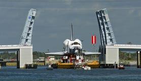 Space shuttle on barge. US Space Shuttle on barge passing through a raised drawbridge Stock Photos
