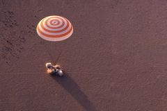 Space shuttle landing in a field by parachute. Elements of this image were furnished by NASA