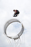 Space wheel performer. A stunt performer performing a hula hooping act while on top a wheel of death or a space wheel circus apparatus. This was performed during Stock Image