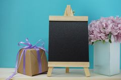 Space wooden easel artist and gift box and artificial peony flowers. Space wooden easel artist and gift box and artificial green plant on wooden background royalty free stock image