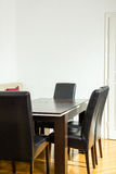 Space for work and business meetings with clients and people. Dining room interior with table and four black chairs near kitchen. Breakfast Area spot. Space for stock photo
