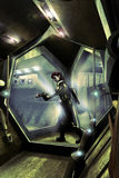 Spacecraft corridors. Woman in a black suit, with a laser gun, walking through futuristic corridors, like if she was searching for something or someone Royalty Free Stock Images