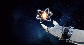 Humankind universe and science. Spaceman hand and atom molecule as science concept. 3d rendering Royalty Free Stock Image