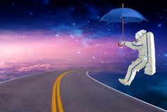 Spaceman lands on an umbrella on the space route. Elements of this image furnished by NASA stock illustration
