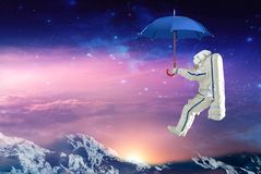 Spaceman on the umbrella traveling in outer space. Elements of this image furnished by NASA stock illustration