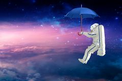 Spaceman on the umbrella traveling witch space mission. Elements of this image furnished by NASA royalty free illustration