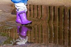 Spaceruje dzieciaka w gumowych butach w kałuży Fotografia Stock