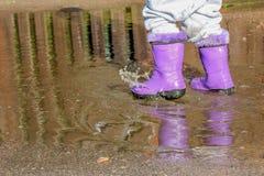 Spaceruje dzieciaka w gumowych butach w kałuży Fotografia Royalty Free