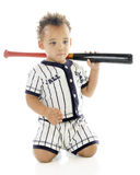 Spacey Ball Player. An adorable biracial 2-year-old with a bat over his shoulder, spacing out in his baseball uniform.  On a white background Royalty Free Stock Photos