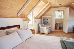 Spacious attic bedroom with bathroom in a home. Interior of a comfortable master bedroom with an en suite bathroom in the loft of a contemporary residential home Royalty Free Stock Images