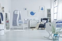 Spacious baby`s room with crib. Vase next to white cradle in spacious baby`s room with blanket on armchair and striped veil above crib Stock Photos