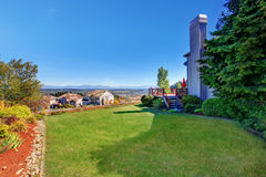 Spacious back yard with grass filled garden and amazing view. Royalty Free Stock Images