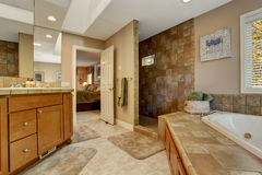 Spacious bathroom with corner bath tub and open shower Royalty Free Stock Photo