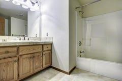 Spacious bathroom interior with bath tub. Wooden cabinet with mirror royalty free stock photos