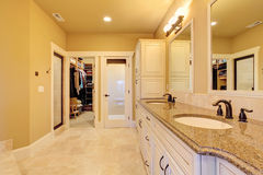 Spacious bathroom with walk-in closet. Soft ivory bathroom interior with tile floor and walk-in closet stock photo