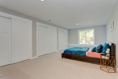 Spacious bedroom with built in closets. In front of a blue bed stock images