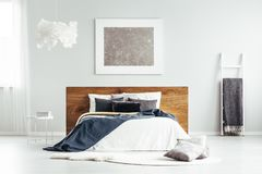 Bedroom with blankets and cushions. Spacious bedroom interior with cloud lamp, white ladder with and simple bed with wooden bedhead, blankets and cushions stock images