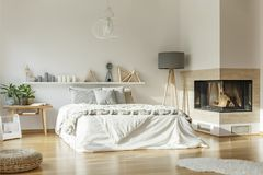 Spacious bedroom with fireplace. Spacious bedroom interior with fireplace, large bed, lamp, rug and ornaments stock photography