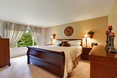 Spacious bedroom interior with nice wooden bed Royalty Free Stock Photos
