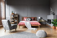 Spacious bedroom interior with pouf and gray armchair in front o. F a pink bed with wooden bedhead. Real photo royalty free stock image