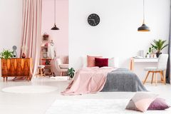 Spacious bedroom with pastel curtain. Spacious bedroom interior with walk-in wardrobe behind pastel pink curtain and bed with pink cushions Stock Photo