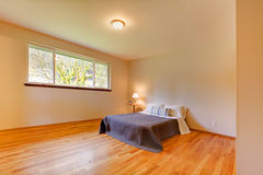 Spacious bedroom with light tones walls and hardwood floor Royalty Free Stock Image