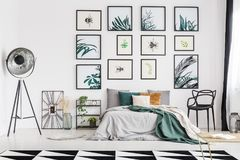 Botanic themed bedroom. Spacious botanic themed bedroom interior decorated with posters of herbs and bugs royalty free stock photos