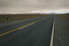 Spacious cloudy landscape crossed by empty road. This shot gives a feel to the wideness and emptiness of this harsh landscape. The road giving a lot of royalty free stock photography