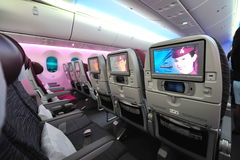 Spacious and comfortable economy class cabin of Qatar Airways Boeing 787-8 Dreamliner at Singapore Airshow Royalty Free Stock Photos