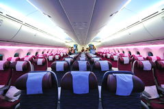 Spacious and comfortable economy class cabin of Qatar Airways Boeing 787-8 Dreamliner at Singapore Airshow. SINGAPORE - FEBRUARY 12: Spacious and comfortable Stock Photo