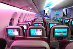 Spacious and comfortable economy class cabin of Qatar Airways Boeing 787-8 Dreamliner at Singapore Airshow. SINGAPORE - FEBRUARY 12: Spacious and comfortable Royalty Free Stock Image