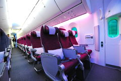 Spacious and comfortable economy class cabin of Qatar Airways Boeing 787-8 Dreamliner at Singapore Airshow Royalty Free Stock Photo