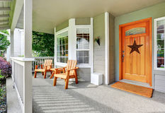 Spacious concrete porch with wooden chairs and nice entry door. Royalty Free Stock Image