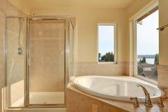 Spacious creamy bathroom with corner bathtub. Royalty Free Stock Photo