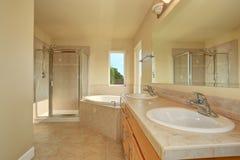Spacious creamy bathroom with corner bathtub. Stock Images