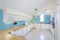 Spacious designer fully fitted kitchen. Contemporary designer fully fitted kitchen in blue and white with breakfast bar and modern appliances Royalty Free Stock Image