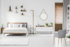 Spacious designer white bedroom interior with wooden bed with be. Dding and pillows, night-table, small shelves above and modern armchair on the right. Real stock images