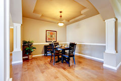 Spacious dining room with white columns and beige tray ceiling. Royalty Free Stock Photography