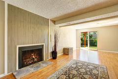 Spacious empty living room with fireplace and exit to the back yard. Stock Photo