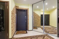 Spacious entrance hall in the apartment with built-in wardrobe and huge mirrors stock photos