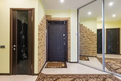 Spacious entrance hall in the apartment with built-in wardrobe and mirrors royalty free stock image