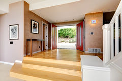 Spacious entrance hallway with open door. Enrance hallway in soft mocha color, with hardwood floor, stairs and red entrance door Stock Photography