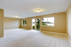 Spacious family room with clean carpet floor and exit to walkout Stock Photo