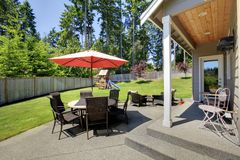 Spacious fenced backyard area with patio table and play set for kids Stock Photo