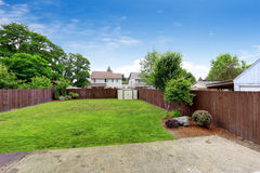 Spacious fenced backyard with shed. Spacious backyard area with  dark brown wooden fence and shed. View from patio area Royalty Free Stock Photography