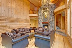 Spacious great room features pine paneled walls. Amazing large stone fireplace and luxurious brown leather sofas Royalty Free Stock Photography