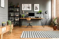 Spacious grey workspace interior. Striped rug near wooden cupboard in spacious grey workspace interior with posters above desk royalty free stock image
