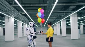 Spacious hall with a cyborg getting balloons from a girl. 4K stock footage