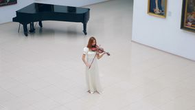 Spacious hall with a woman playing the violin in it stock video footage